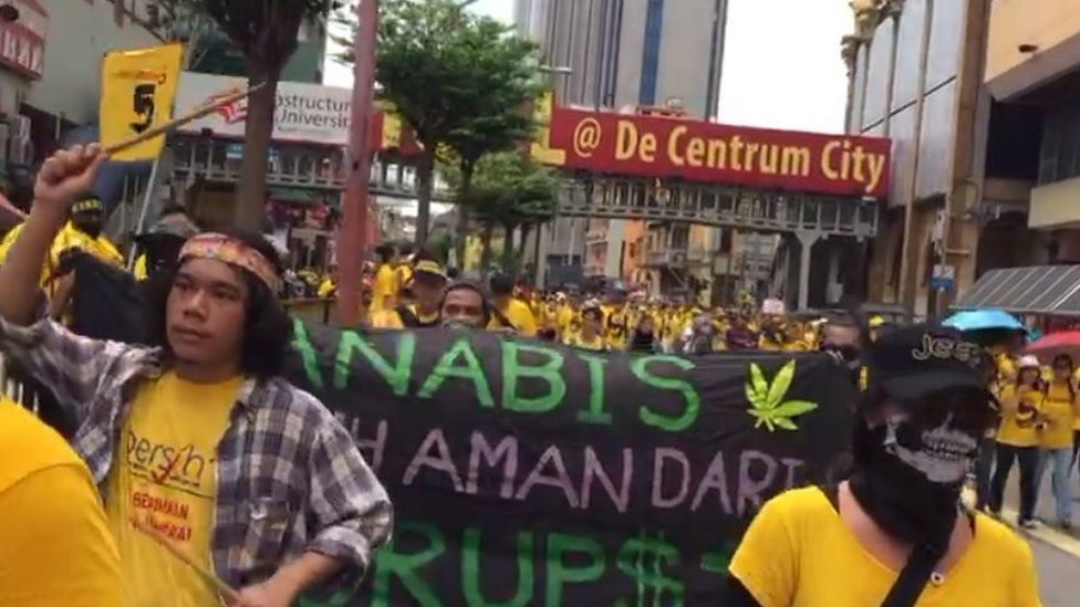 Protesters at a rally carry a sign calling for tough penalties against cannabis possession to be scrapped