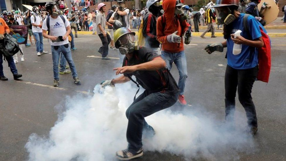 A demonstrator prepares to throw a tear gas canister during riots at a rally against Venezuelan President Mauro's government in Caracas, Venezuela, June 7, 2017.