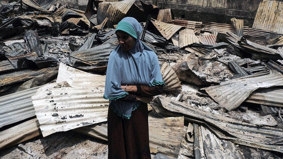 A woman stands beside the rubble that was once her stall at the market place in Fakfak, West Papua