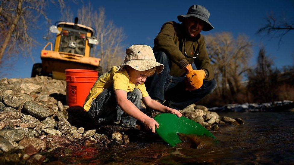 panning for gold along Clear Creek Whitewater Park in Golden. Colorado