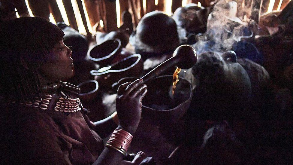 A woman from the Hamar tribe makes traditional coffee in Ethiopia's southern Omo Valley region near Turmi on September 20, 2016.