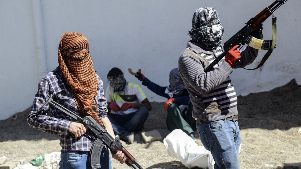 Kurdish militants stand behind a barricade during fighting with Turkish forces