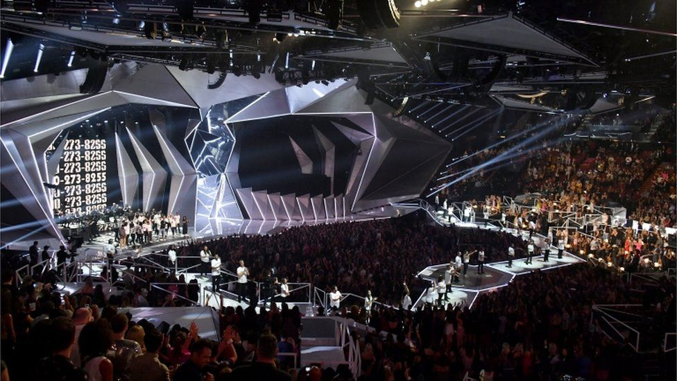Logic, Alessia Cara, Khalid, and special guests perform onstage during the 2017 MTV Video Music Awards (A stage is shown lined with survivors and surrounded by crowds)