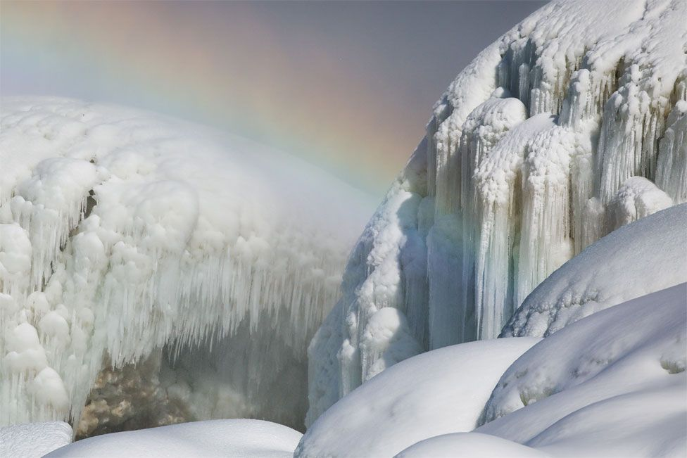 A rainbow can be seen alongside huge icicles at Niagara Falls
