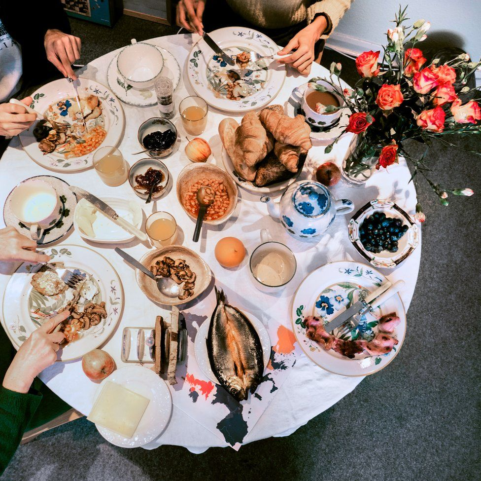 An image of a spread of breakfast food with people eating