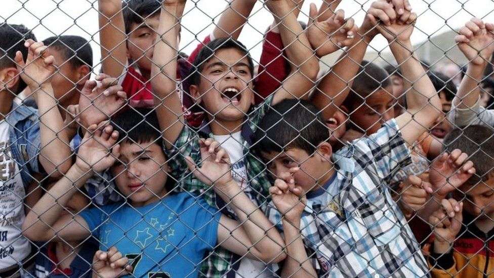 Syrian refugee children stand behind a fence at the Nizip migrant camp in Turkey. Photo: April 2016