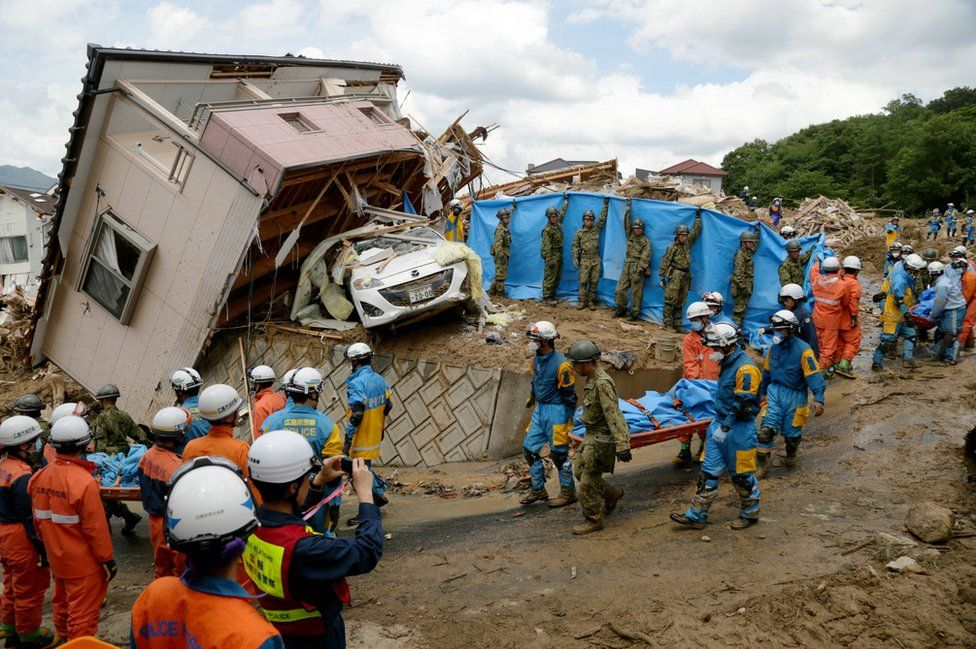 Police and Ground Self-Defense Force's rescue workers carry a victim away after they were killed by a landslide caused by heavy rains in Kumano, Hiroshima Prefecture, Japan