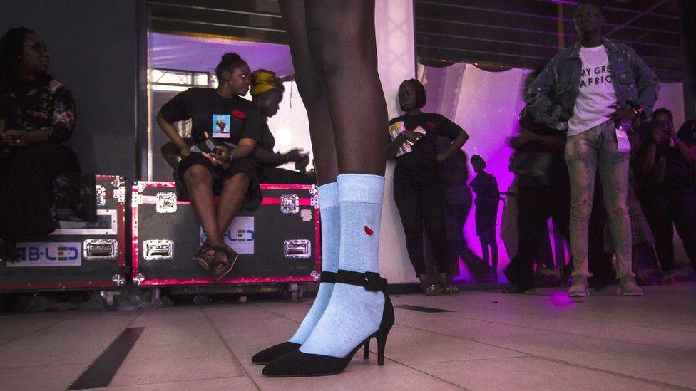 Un mannequin en chaussettes et hauts talons dans les coulisses de la Semaine de la mode de Dakar à Dakar, Sénégal