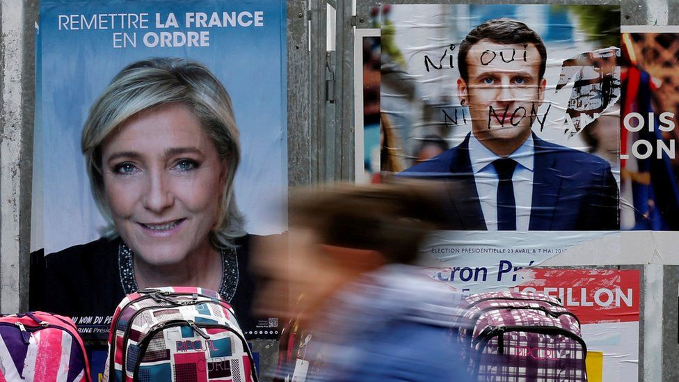 A woman walks past official posters of candidates for the 2017 French presidential election