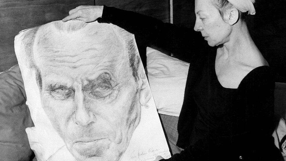 Lucette Destouches holds up a portrait of her husband Louis-Ferdinand Céline in 1969