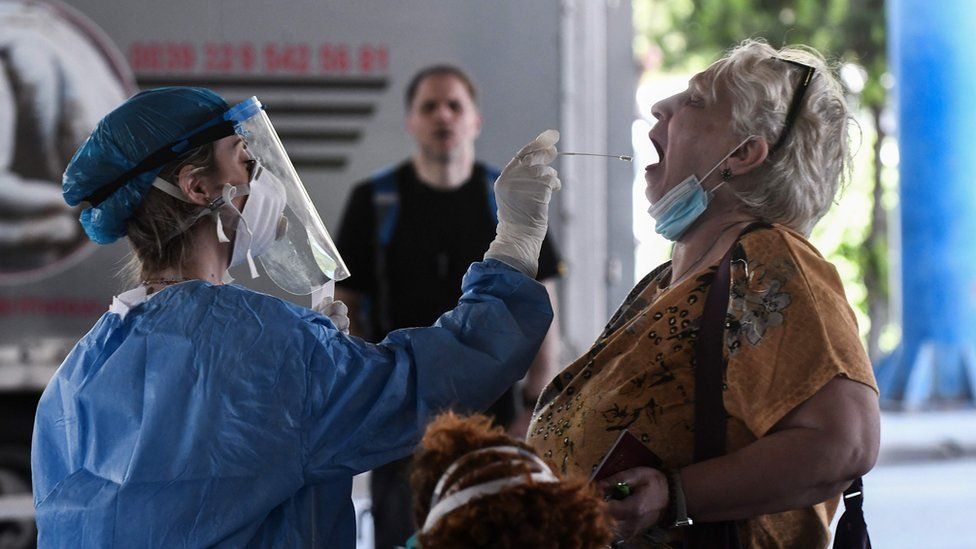 A public health worker collects a swab sample from a woman to test for the COVID-19 coronavirus at the Greek-Bulgarian border crossing in Promachonas on June 19, 2020