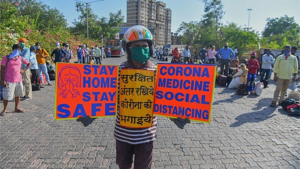 Social worker Surender holds placards to create awareness about social distancing in Mumbai on May 11, 2020