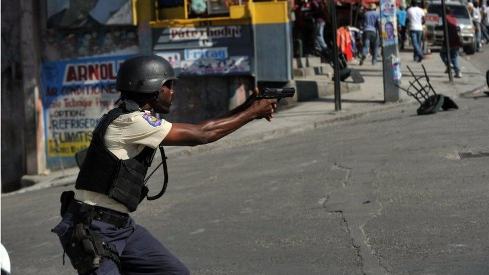 A Haitian policeman aims his gun during clashes with demonstrators in Port-au-Prince on 24 November, 2015.