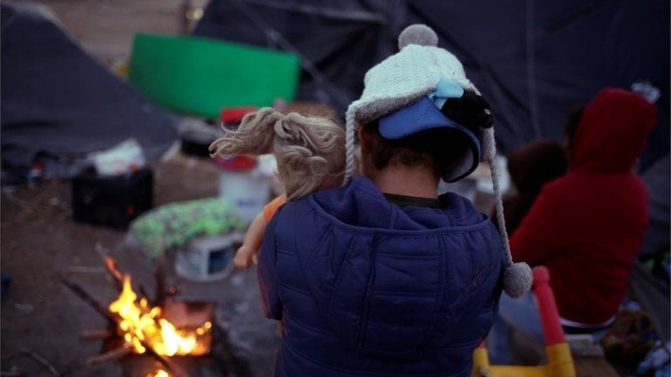 A Mexican girl hugs a doll in a make-shift camp in Ciudad Juarez