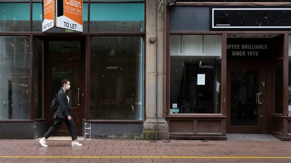 A woman walking along Cardiff street with empty shops behind