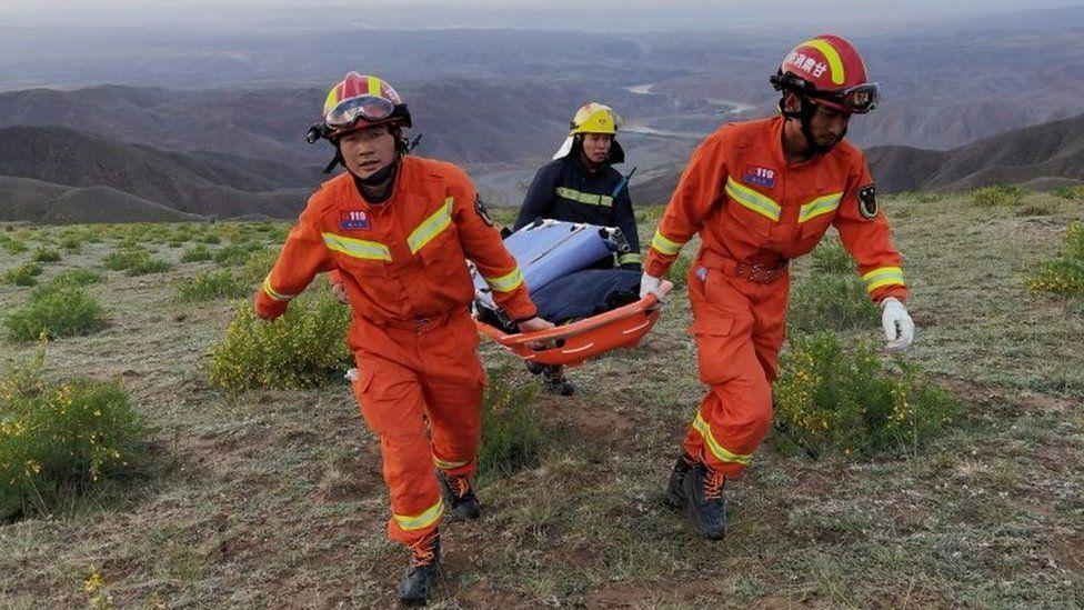 Rescuers carry a stretcher at the site of the ultra-marathon race in Gansu