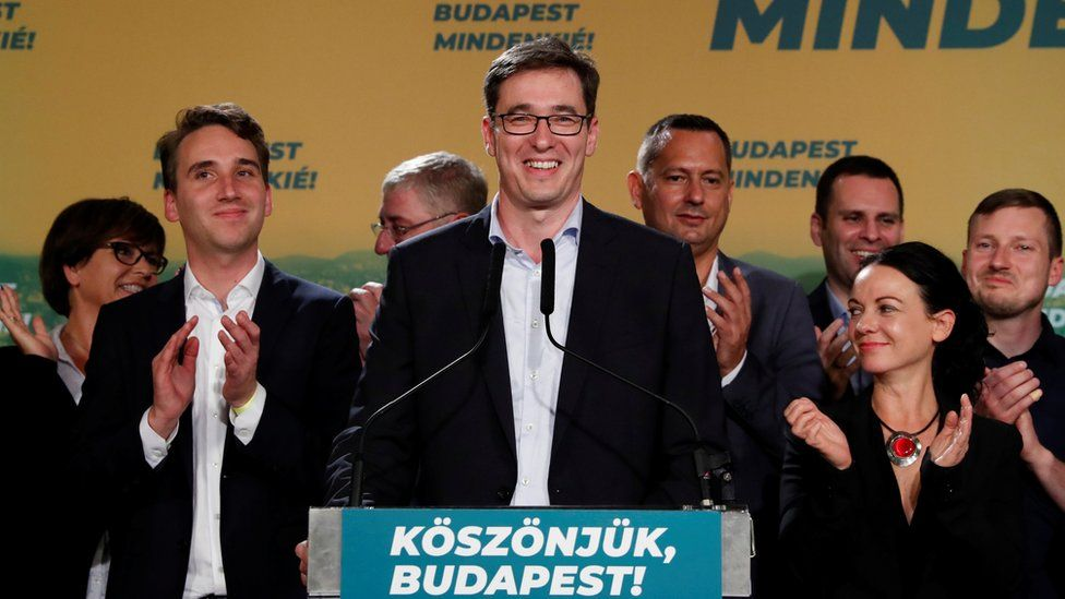 Newly elected Budapest mayor Gergely Karacsony stands smiling at a podium following his win