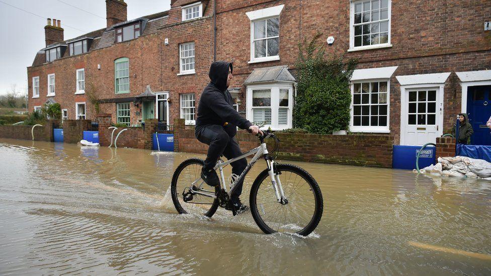 A man rides a bike through flood water, in Tewkesbury