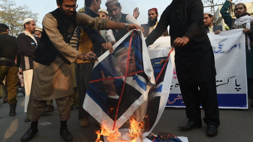 Pakistani demonstrators burn images of US President Donald Trump and the US flag during a protest against US aid cuts in Lahore on January 5, 2018.