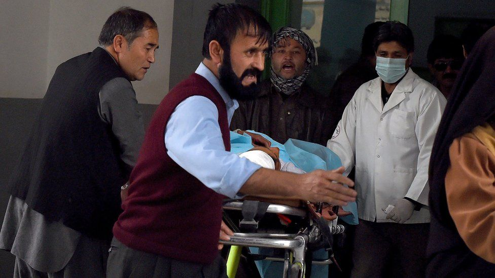 Afghan relatives and doctors move a wounded Afghan man at the Estiqlal Hospital after a massive suicide blast at a Shia mosque in Kabul on 21 November 2016