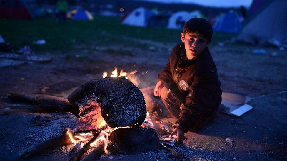 Refugee child at bonfire in makeshift camp at the Greek-Macedonian border near village of Idomeni, on March 3, 2016