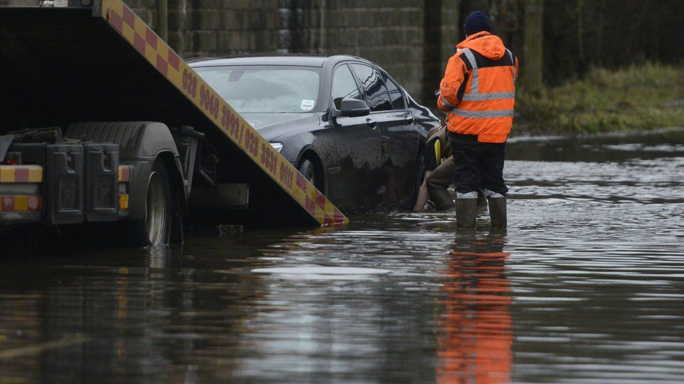 Vehicle recovery staff work to remove a car stranded on a flood-hit road