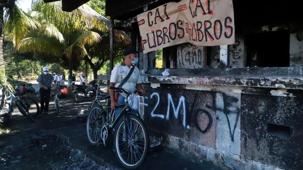 "A man looks at a police station burned down during the protests against what they demonstrators say was police brutality exerted in recent protests against President Ivan Duque""s government""s tax reform in Cali, Colombia May 3, 2021."