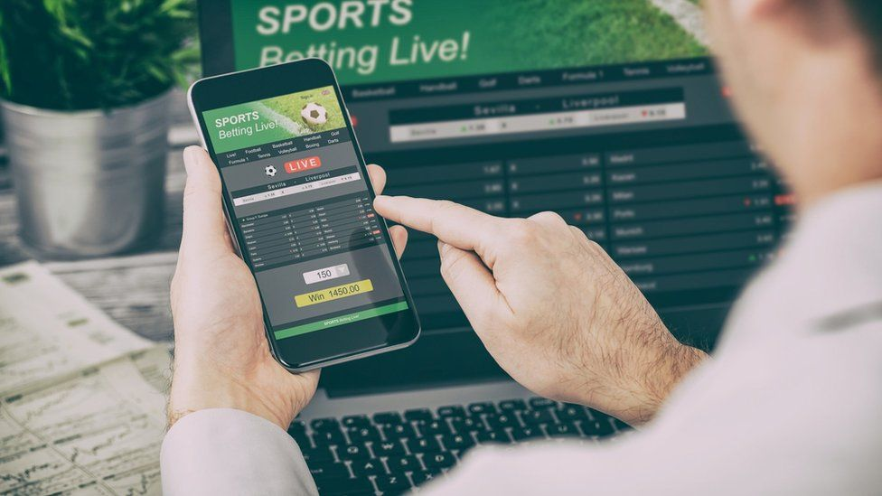 A man betting on football using his mobile phone.
