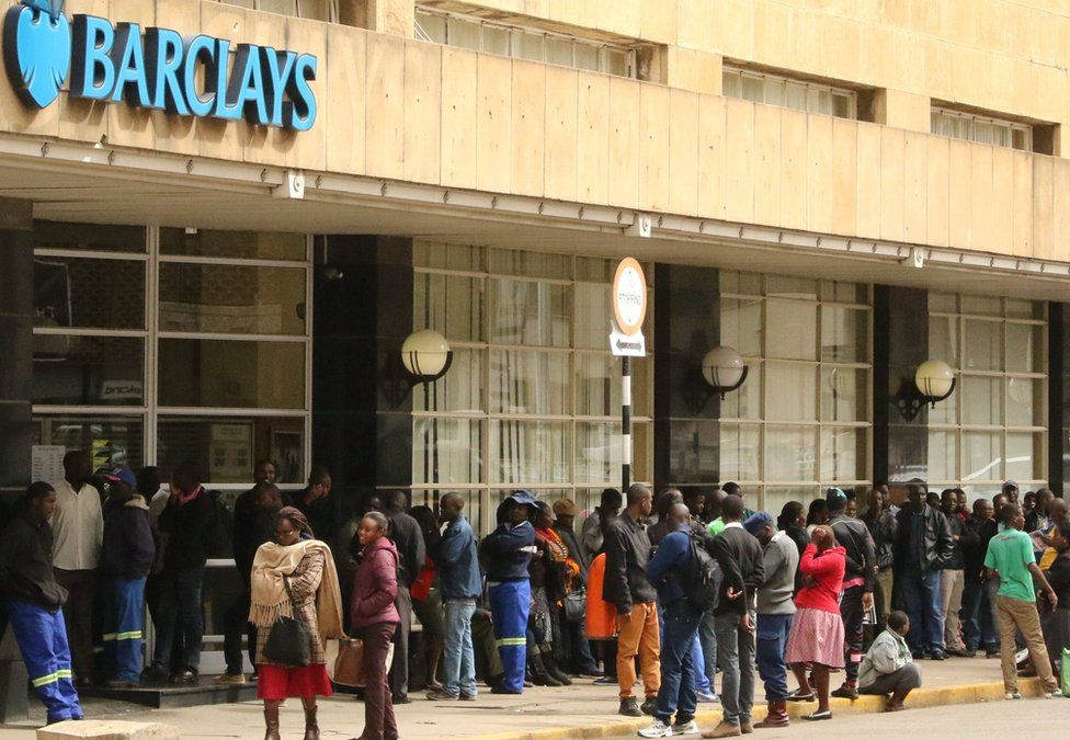 People queue to withdraw cash from a branch of Barclays bank in Harare, Zimbabwe