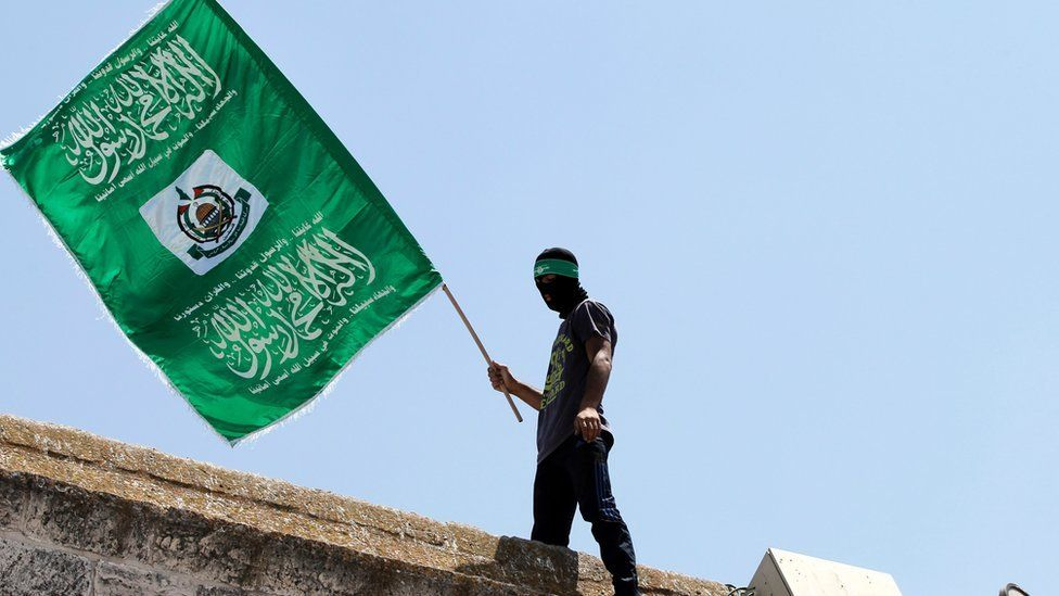a man silhouetted on a Jerusalem roof, waving the Hamas flag