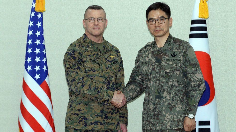 South Korea's Major General Jang Kyung-soo (R) and US Forces Korea Major General Robert Hedelund shake hands at the Defense Ministry in Seoul
