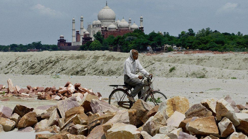 An Indian man rides a bicycle past rocks that were to be used at a construction near the Taj Mahal in 2003
