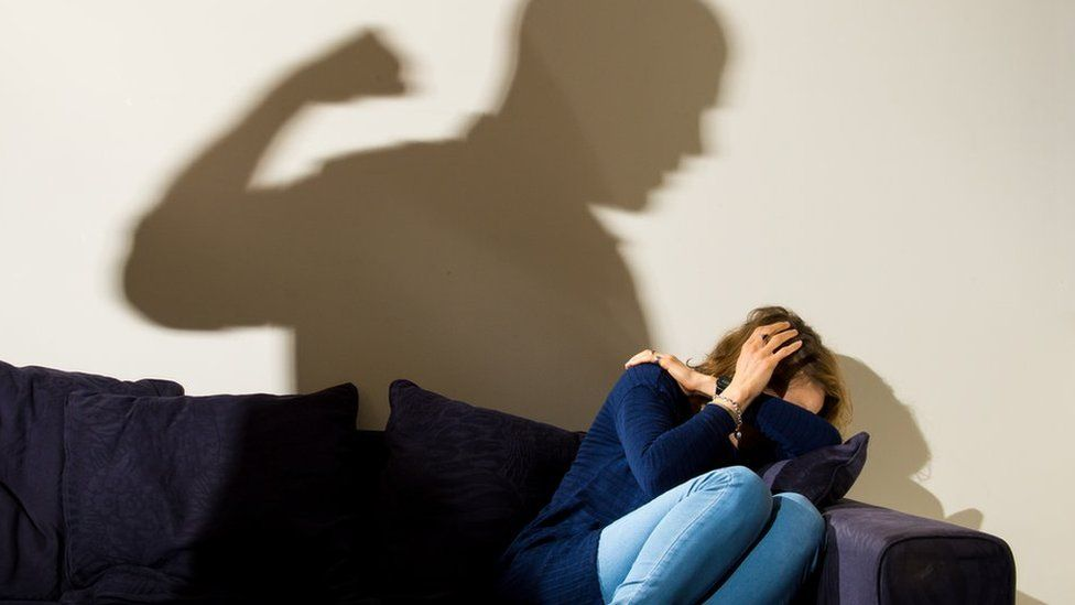 Image showing silhouette of a man with a clenched fist threatening a frightened woman (posed by models)