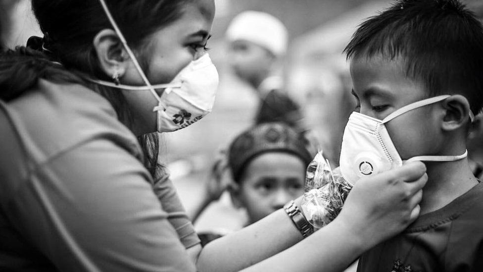 A volunteer helps a child put on an N95 face mask