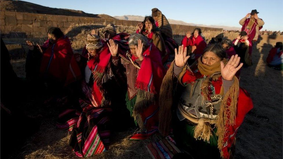 Aymara indigenous hold up their hands to receive the first rays of sunlight in a New Year's ritual in the ruins of the ancient city Tiwanaku, Bolivia, early Tuesday, June 21, 2016.