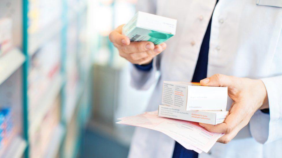pharmacist takes box of pills from shelf