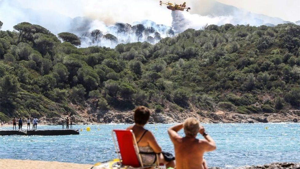 People sit on the beach as they look at Canadair aircraft dropping water over a fire in La Croix-Valmer, near Saint-Tropez. Photo: 25 July 2017
