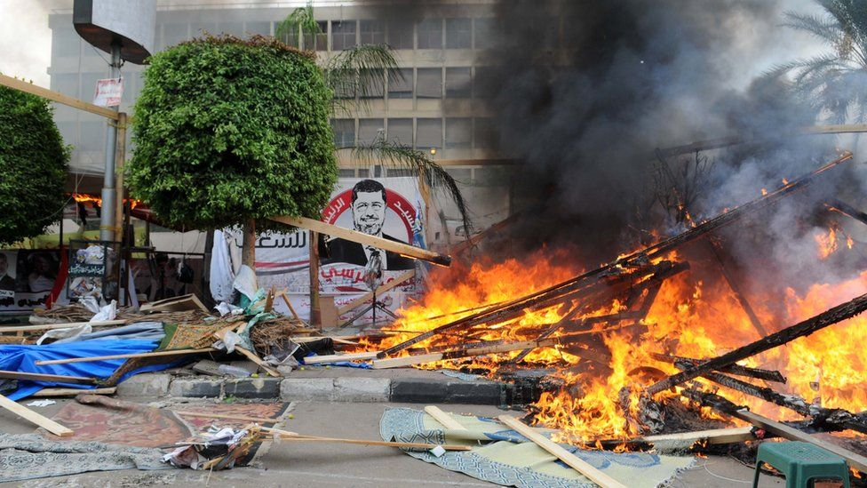 Security forces break up a sit-in by supporters of Mohammed Morsi in Cair's al-Nahda Square (14 August 2013)