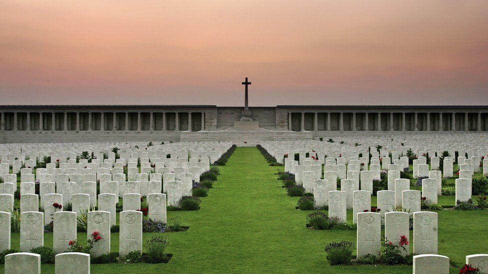The grave stone of soldiers killed in the Battle of Somme line up at sunset at the Pozieres Memorial