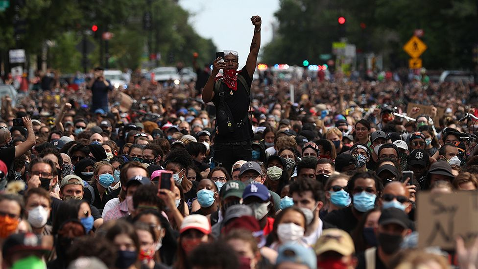 A man holds up his fist while hundreds of demonstrators march to protest against police brutality and the death of George Floyd, on June 2, 2020 in Washington, DC.