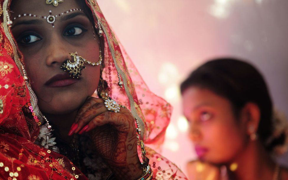 An Indian bride (L) waits with her sister (R) for her wedding ceremony.