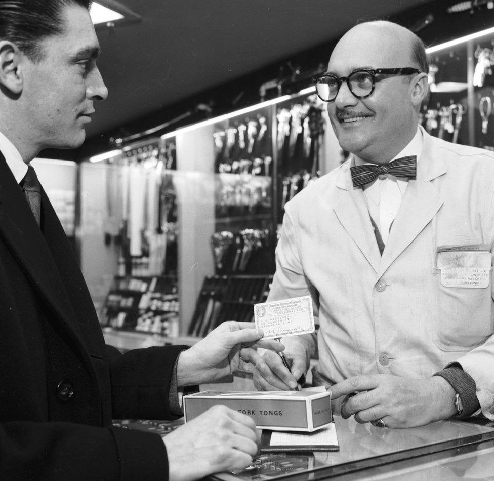 A customer pays with an American Express card in a cutlery shop in Manhattan, circa 1955