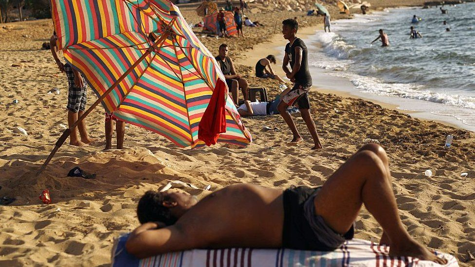 Libyans rest and swim at a beach in the eastern coastal Libyan city of Benghazi