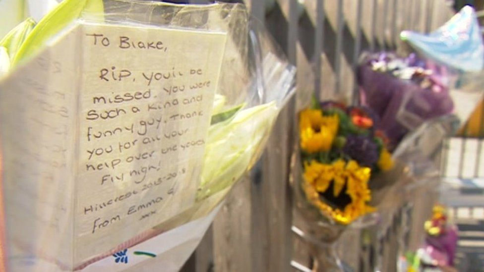Flowers and messages pinned to gates at school