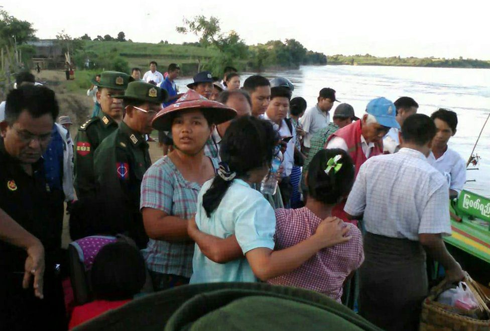 In this handout photograph released by the Myanmar Fire Services Department on October 17, 2016, relatives watch as rescue personnel prepare to search for victims of a ferry that capsized near Monywa city in Sagaing region.