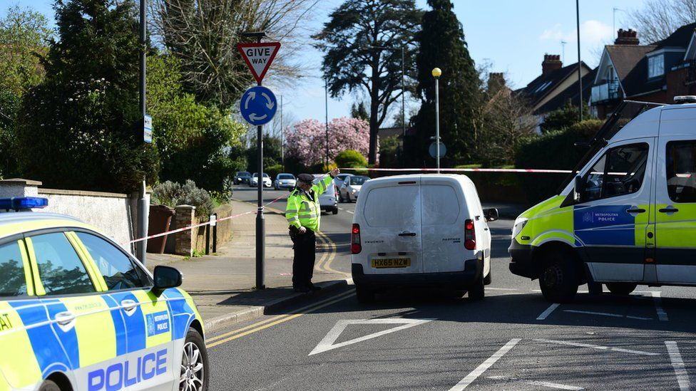 Officer lifting up a cordon in Marsh Road