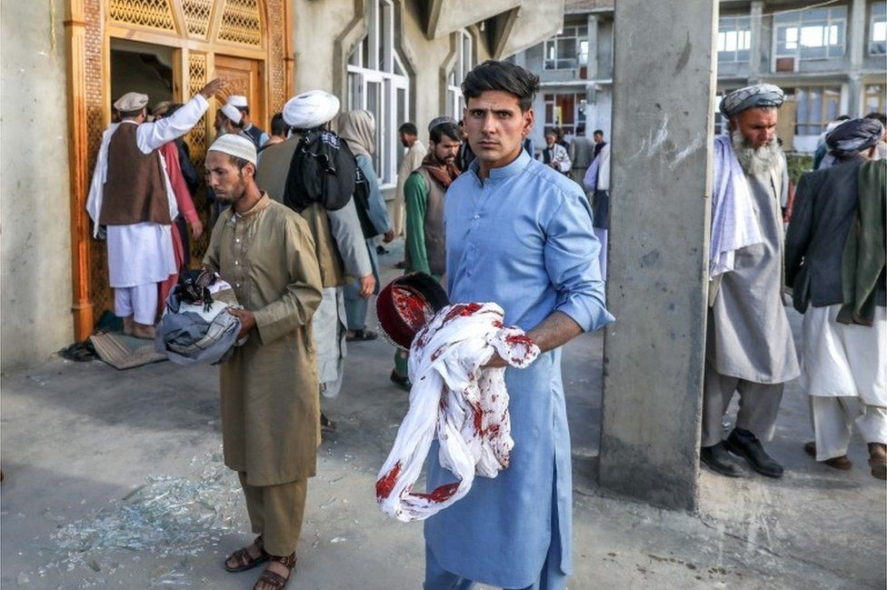 Afghan men hold the belongings of worshippers at the scene of an attack that targeted a mosque in the outskirt of Kabul, Afghanistan, 14 May 2021.