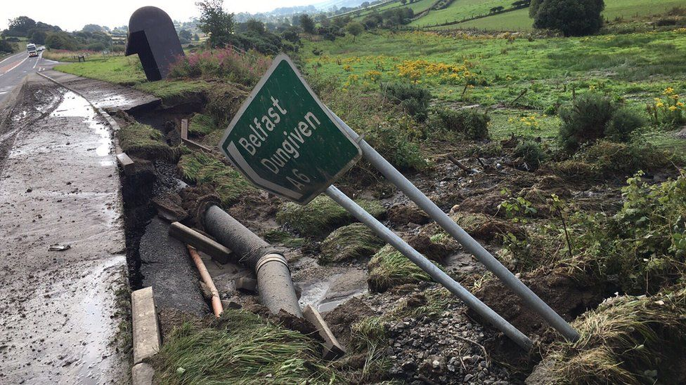 A fallen sign pointing the way to Belfast and Dungiven