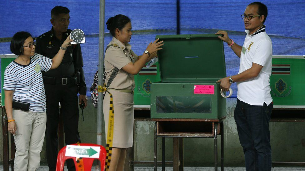 Officials over see ballot boxes during Thailand's referendum