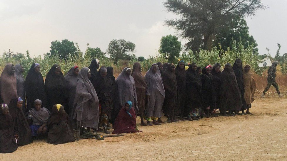 A man carrying a Boko Haram flag walks past a group of 82 Chibok girls, who were held captive for three years by Islamist militants, as the girls wait to be released in exchange for several militant commanders